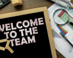 Text Welcome to the team on the blackboard on the desk with office business accessories